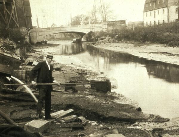 n the late 1800s and early 1900s Philadelphia was infamous for having some of the most polluted rivers in the country, and thus some of the worst public water supplies. This 1928 photo shows wastes in Bridgeport Canal below the outlet of March Packing Company.  The Canal fed into the Schuylkill River, from which Philadelphia received much if its drinking water.  The investigator in the picture holds a pig gut on the end of the pole. Source: Philadelphia Water Department Historical Collection
